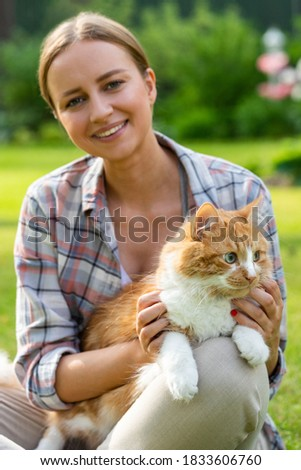 Close up of smiling woman in checked shirt looking at camera, hugging and embracing with tenderness and love domestic ginger cat outdoors. Love to the animals, pets. Defocused, selective focus.