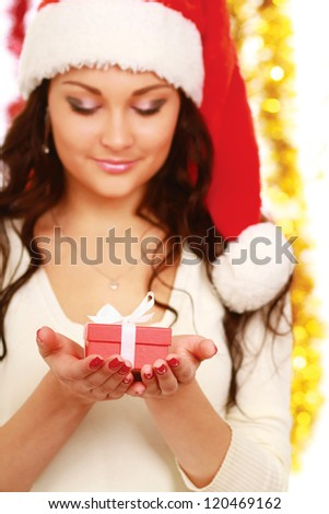 Close-up of smiling woman with gift isolated on christmas decorated background
