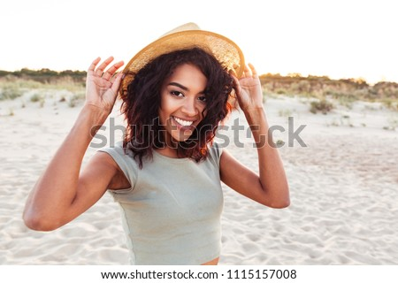 Close up of smiling young african girl in summer hat looking at camera at the beach #1115157008
