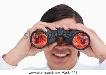 Close up of smiling young tradesman looking through binoculars against a white background