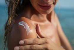 Close up of smiling young woman is applying a sunscreen or sun tanning lotion on a shoulder to take care of her skin on a seaside beach during holidays vacation.