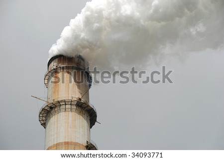 Close-up of smoke stack against a gray sky.