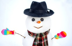 Close up of snowman standing in hat and scarf with red nose. Snow man isolated on white
