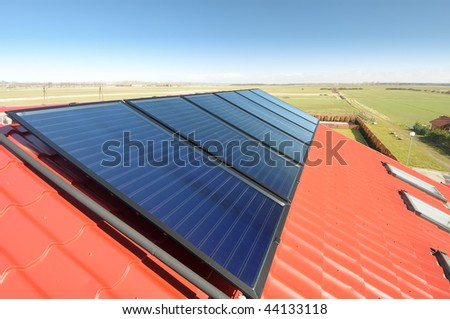 Close up of solar panels on red tiled roof and beautiful blue sky.