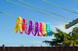 Close up of some colorful laundry clips/clothespins/clothes pegs on outdoor clotheslines against the garden fence and clear blue sky. Concept of a beautiful sunny summer day and housework.