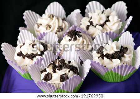 Close up of some decadent gourmet cupcakes with chocolate and vanilla frosting. Shallow depth of field.