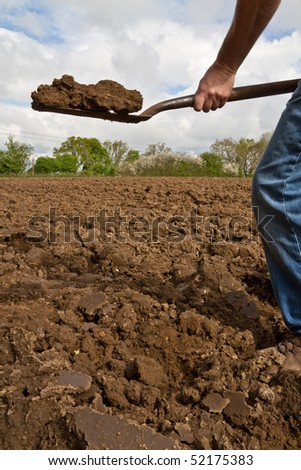 Close up of someone lifting a spadeful of soil in the process of digging - stock photo