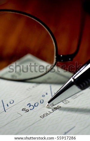 Close up of someone writing a check to pay the bill.
