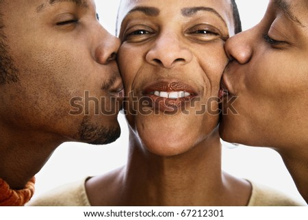 Close up of son and daughter kissing mother