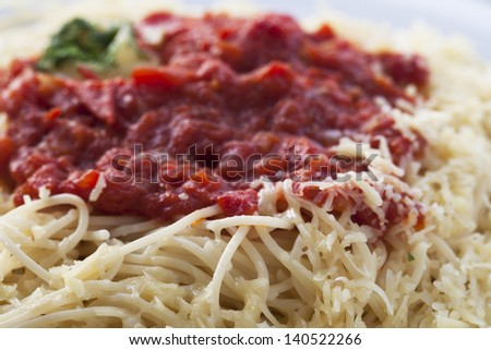 Close up  of spaghetti topped with tomato sauce and grated cheese