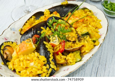 Close-up of Spanish paella on white plate - stock photo