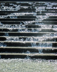 Close-up of sparkling water spashing down concrete stairs in a fountain into pool below  with water drops in the air