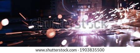 Close up of sparks fly out machine head for metal processing at the factory. Automotive production concept