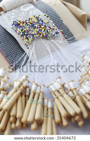 Close-up of special lace making pin cushion. Pins and wooden bobbins for lace making. Traditional craft in many countries in Europe