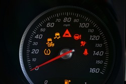Close up of speedometer dial with warning lights on a car