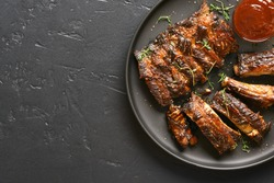 Close up of spicy grilled spare ribs on plate over dark stone background with copy space. Top view, flat lay