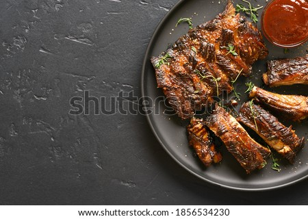 Close up of spicy grilled spare ribs on plate over dark stone background with copy space. Top view, flat lay Foto stock ©