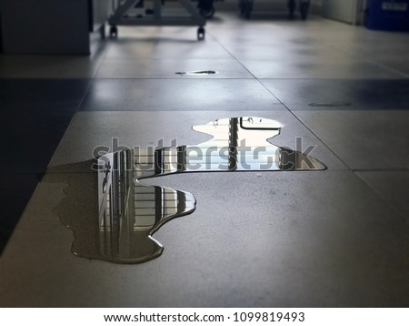 Close-up of spilled water leak on the floor of building. Wet floor from rainy splash or pipelines water leakage in house. Danger accident at home from slippery floor hazard concept. #1099819493