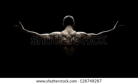 Close up of sports man's muscular back isolated on black background