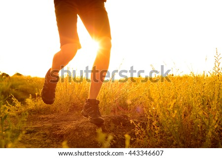 Close-up of Sportsman's Legs Running on the Rocky Mountain Trail at Sunset. Active Lifestyle Concept #443346607