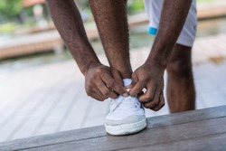 Close-up of sportsman tying laces on his training shoes