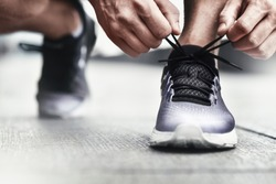 Close-up of sportsman tying sneakers. Unrecognizable man stopping lacing shoe outdoors. Athletic shoes concept. Color Version
