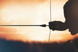 Close up of sportswoman practising archery on a white background against orange sunrise