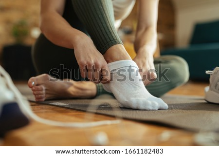 Close-up of sportswoman wearing white socks while preparing for workout at home.  Foto stock ©