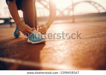 Close up of sporty caucasian woman kneeling and tying shoelace on court in the morning. Sometimes the best runs come on days you didn't feel like running.
