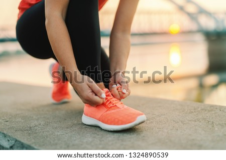 Close up of sporty woman tying shoelace while kneeling outdoor, In background bridge. Fitness outdoors concept.