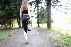 Close-up of sporty young woman training in summer forest. Fit and strong female doing exercise far away from people. Lady in trendy comfy sportswear. Sport and hobby concept