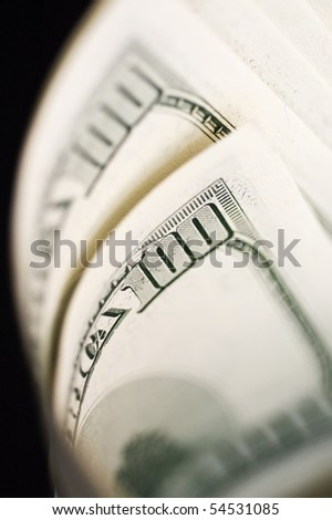 Close Up of Stack of dollars isolated on black background.