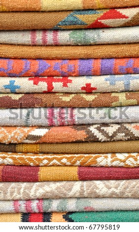 close up of stacked  folded colorful carpets