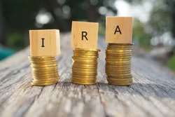 Close up of stacking gold coins and wooden blocks written IRA on nature background and natural lighting. Individual Retirement Accout concept