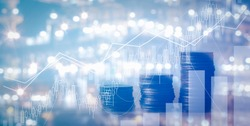 Close up of stacking of growth up coins with Double exposure of chart graph and night shift of oil and gas platform for finance and business ,capital banking and investment concept.