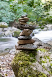 Close up of stacks of rocks on the river bank in a forest