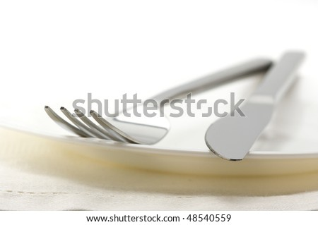 Close-up of stainless fork and knife on white plate with linen napkin. Selective focus on foreground.