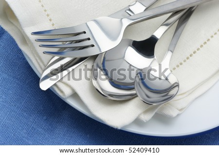 Close-up of stainless spoon, fork and knife on plate with linen napkin.