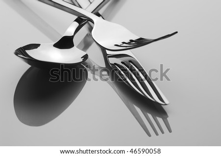 Close-up of stainless spoon, knife and fork on light background with shadows. B&W.
