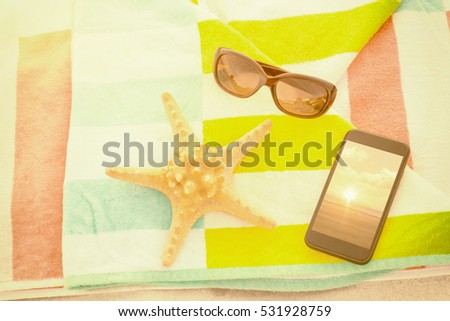 Close up of starfish with sunglasses and mobile phone kept on beach blanket against a beautiful on a beach #531928759