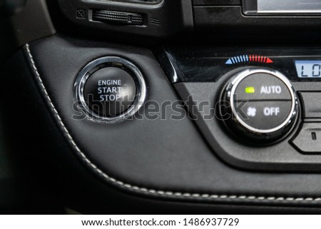 Close-up of start stop engine  button. modern car interior: parts, buttons, knobs. Soft focus