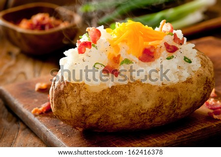 Close up of steaming hot baked potato topped with bacon, green onions and cheddar cheese.