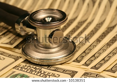 Close-up of stethoscope and one hundred dollars bills