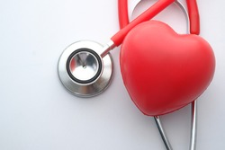 close up of stethoscope and red heart on wooden table. Cardiology concept