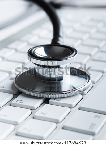 Close up of stethoscope on laptop keyboard. Medicine concept