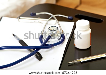 Close-up of stethoscope, pen, paper, medicine and clinical thermometer
