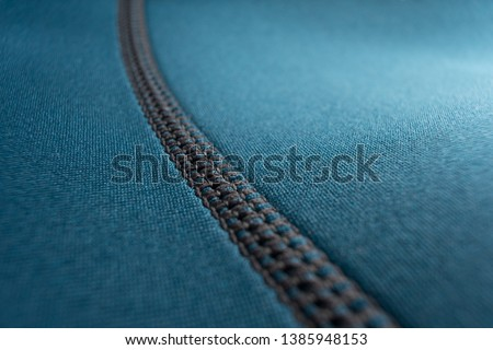 Close up of stitching along the seam of a blue neoprene scuba diving wetsuit #1385948153