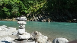 Close up of stone pyramid near beautiful blue mountain river. Balanced stones like a concept of harmony and balance.