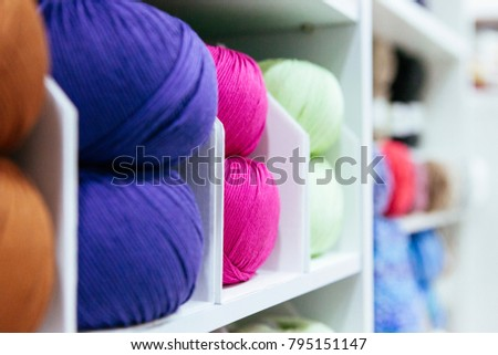 close up of storage wool yarns organized by color on a white shelf #795151147