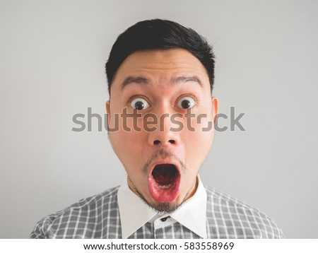 Close up of straight face of surprised and shocked Asian man with light beard. #583558969